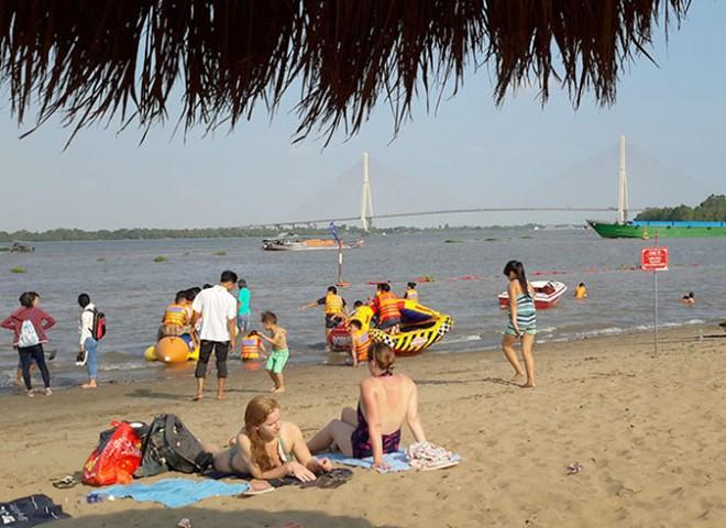 Du khách nước ngoài trên bãi cát sông Hậu - Ảnh: Phương Nguyên.