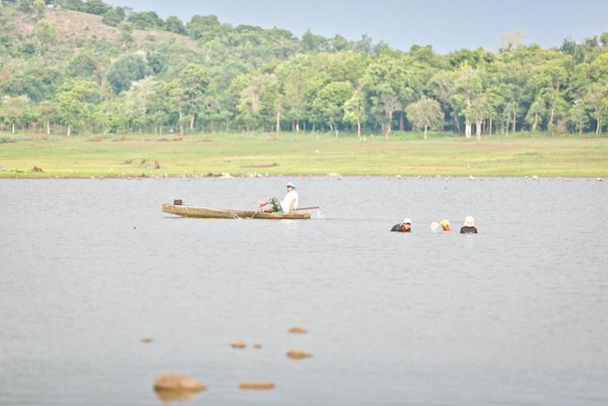 Người dân bơi thuyền gỗ mưu sinh trên hồ Ea Kao