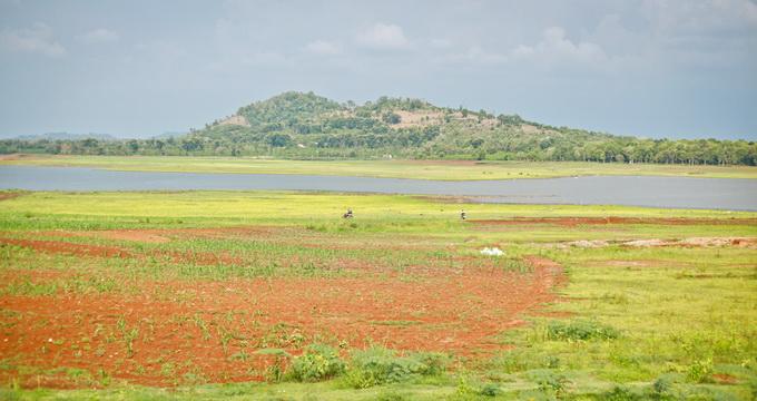 Mực nước hồ Ea Kao đang ở mức thấp để lộ những doi đất đỏ quanh mặt hồ