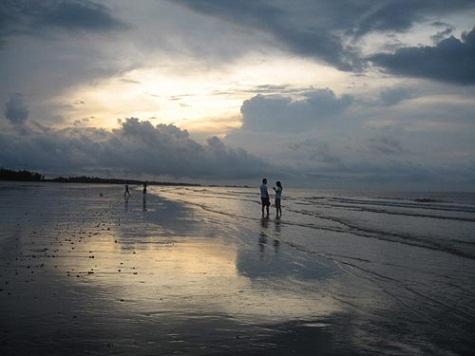 Những đôi lứa yêu nhau tận hưởng vẻ đẹp của bình minh trên biển