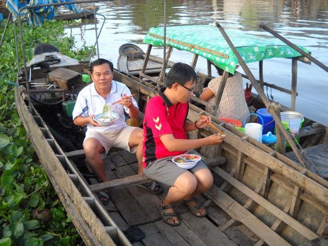 Du khách thưởng thức món ăn trên thuyền.