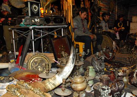 Tại chợ, nhiều chủ gian hàng quảng cáo những món đồ cổ với giá tiền triệu.