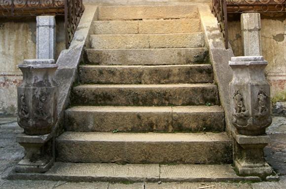 Hai cột bên thành cầu thang đi lên được khắc chạm những hình tượng tôn giáo