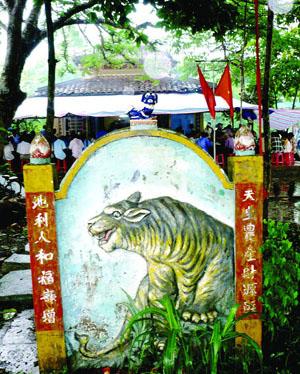 Bức bình phong tạc hình hổ đặt trước đình Tân Hưng, phía sau bình phong là bàn thờ thần Nông