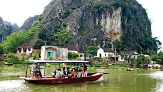 Du khách vào thăm động sẽ đi bằng thuyền từ bến sông Hoàng Long