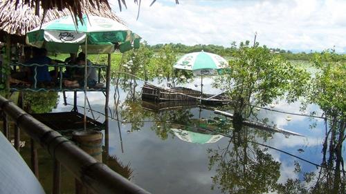 Du khách ngồi trên những chiếc chòi bao quanh là hồ nước rộng lớn