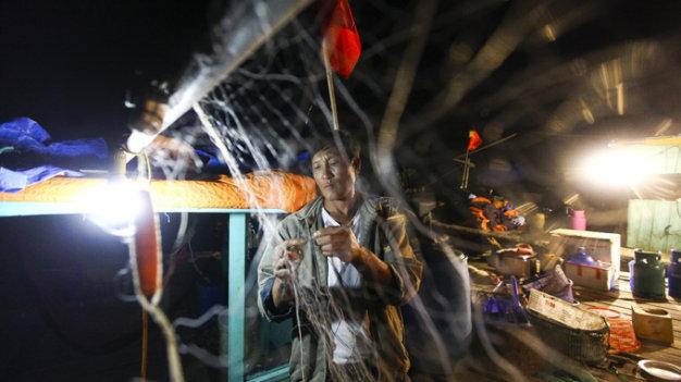 Ông Lê Văn Quang chuẩn bị lưới cho chuyến đánh bắt thủy sản vào ban đêm
