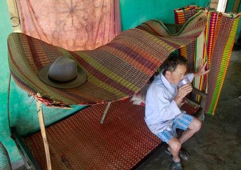 Ông Lê Công ngồi trầm ngâm bên những lá chiếu đã kỳ công hoàn thành mà chưa có thương lái đến mua