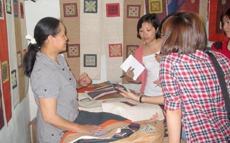 Bà Vàng Thị Mai, Chủ nhiệm HTX đang giới thiệu với du khách về các loại sản phẩm dệt, thêu bằng sợi lanh truyền thống địa phương Quản Bạ.