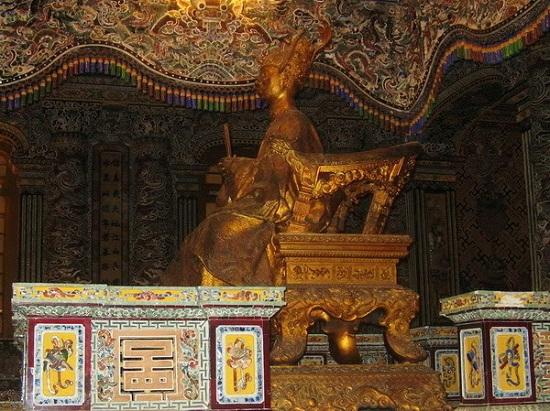 Tượng Vua đồng ngồi trên ngai, phía dưới là thi hài của Vua