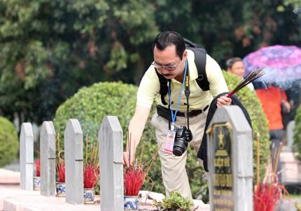 Một phóng viên người Nhật Bản thắp hương trên mộ phần các liệt sỹ.