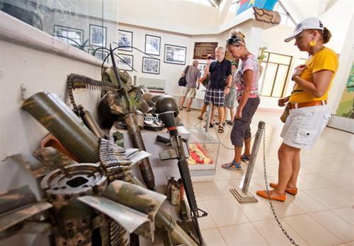Du khách nước ngoài tham quan những trang bị, vũ khí sót lại của lính Mỹ trong nhà bảo tàng đường 9 - Khe Sanh - Ảnh: Tiến Thành