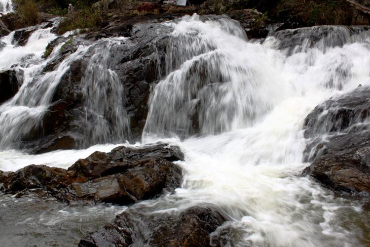Nước chảy xuống xói vào đá tạo bọt trắng xóa...