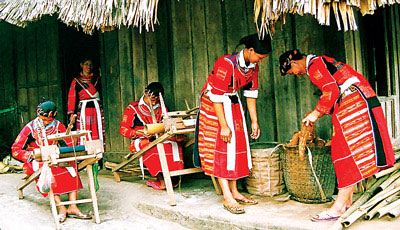 Phụ nữ Dao đỏ chuẩn bị hàng mang ra chợ. Bên cạnh là các cô gái với khung dệt thổ cẩm truyền thống