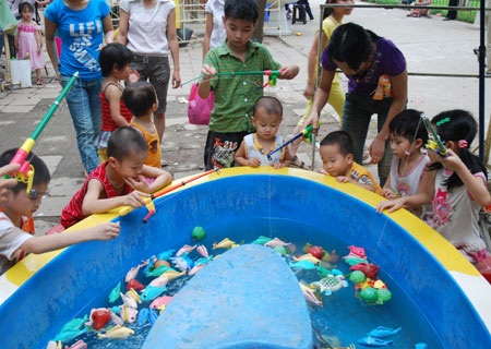 Hàng chục trẻ nhỏ háo hức quây quanh chiếc bể nhỏ để câu cá giả.